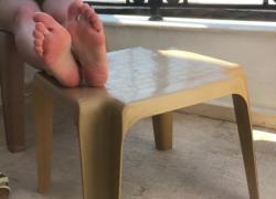Ноги и киска, показывая, что она играет с ногами и киской на общественном балконе