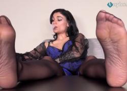Сексуальная брюнетка курит с поднятыми ногами